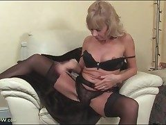 Mature blond Cathy Oakley disrobes to black lingerie
